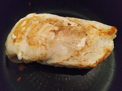 フライパンで鶏肉の両面を焼く写真