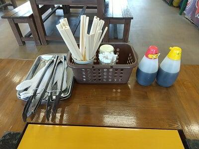 かき小屋 匠ちゃんのテーブルセットに軍手とトングがある写真