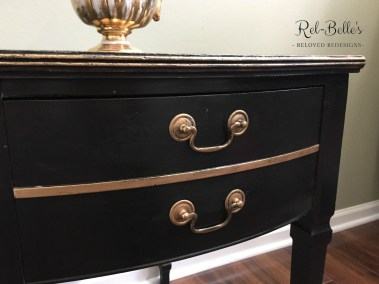 The front of the black and gold side table