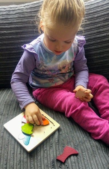 Izzy playing with Hape's George Luck rainbow rabbit puzzle