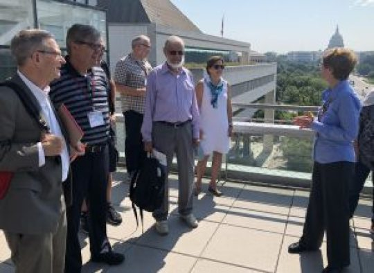 The U.S. Capitol dome appears in the background of this scene in which a guide explaining things to five journalists.
