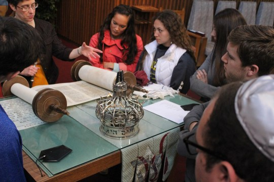Six students crowd around an altar as a rabbi shows them what a Torah scroll looks like and explains how they are created and used.
