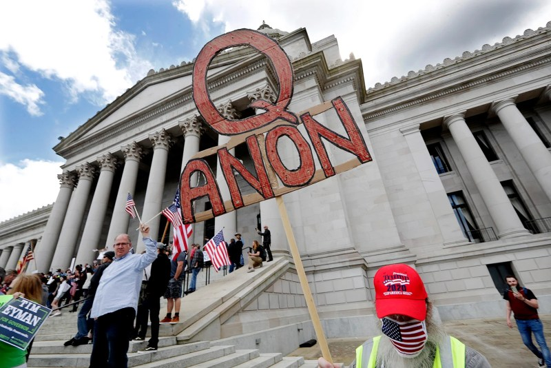 """A demonstrator holds a QAnon sign as he walks at a protest opposing Washington state's stay-at-home order to slow the coronavirus outbreak April 19, 2020, in Olympia, Washington. Washington Gov. Jay Inslee had blasted then-President Donald Trump's calls to """"liberate"""" parts of the country from stay-at-home and other orders designed to combat the spread of the coronavirus. Inslee said Trump was fomenting a potentially deadly """"insubordination"""" among his followers before the pandemic is contained. (AP Photo/Elaine Thompson)"""