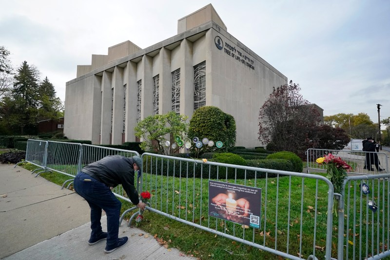 A man places flowers outside the Tree of Life Synagogue in Pittsburgh on Tuesday, Oct. 27, 2020, the second anniversary of the shooting at the synagogue that killed 11 worshippers. (AP Photo/Gene J. Puskar)