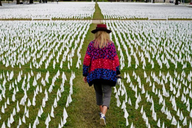 Artist Suzanne Brennan Firstenberg walks among thousands of white flags planted in remembrance of Americans who have died of COVID-19, on Oct. 27, 2020, near Robert F. Kennedy Memorial Stadium in Washington. (AP Photo/Patrick Semansky, File)