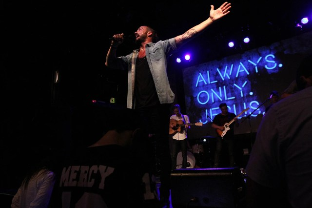 In this July 14, 2013 photo, then-pastor Carl Lentz leads a Hillsong NYC Church service at Irving Plaza in New York. With his half-shaved head, jeans and tattoos, Lentz doesn't look like the typical religious leader. But with its concert-like atmosphere and appeal to a younger demographic, his congregation, Hillsong NYC, is one of the fastest-growing evangelical churches in the city. (AP Photo/Tina Fineberg)