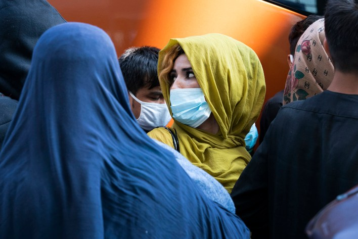 People evacuated from Kabul, Afghanistan, wait to board a bus after they arrived at Washington Dulles International Airport, in Chantilly, Va., on Wednesday, Aug. 25, 2021. (AP Photo/Jose Luis Magana)