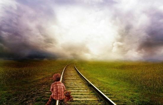child sitting on railway tracks