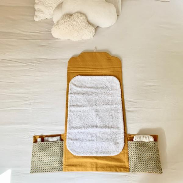 tapis à langer nomade déplié sur un lit