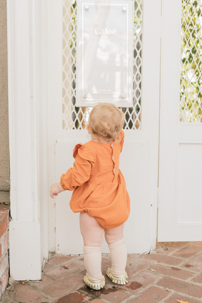 Los Angeles blogger, RELish By Arielle's daughter, Naiya wears an orange onesie with ruffles
