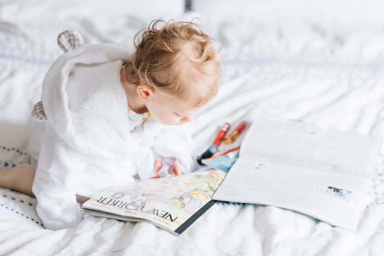 LA blogger, RELish By Arielle's daughter reads magazines in a baby bath robe