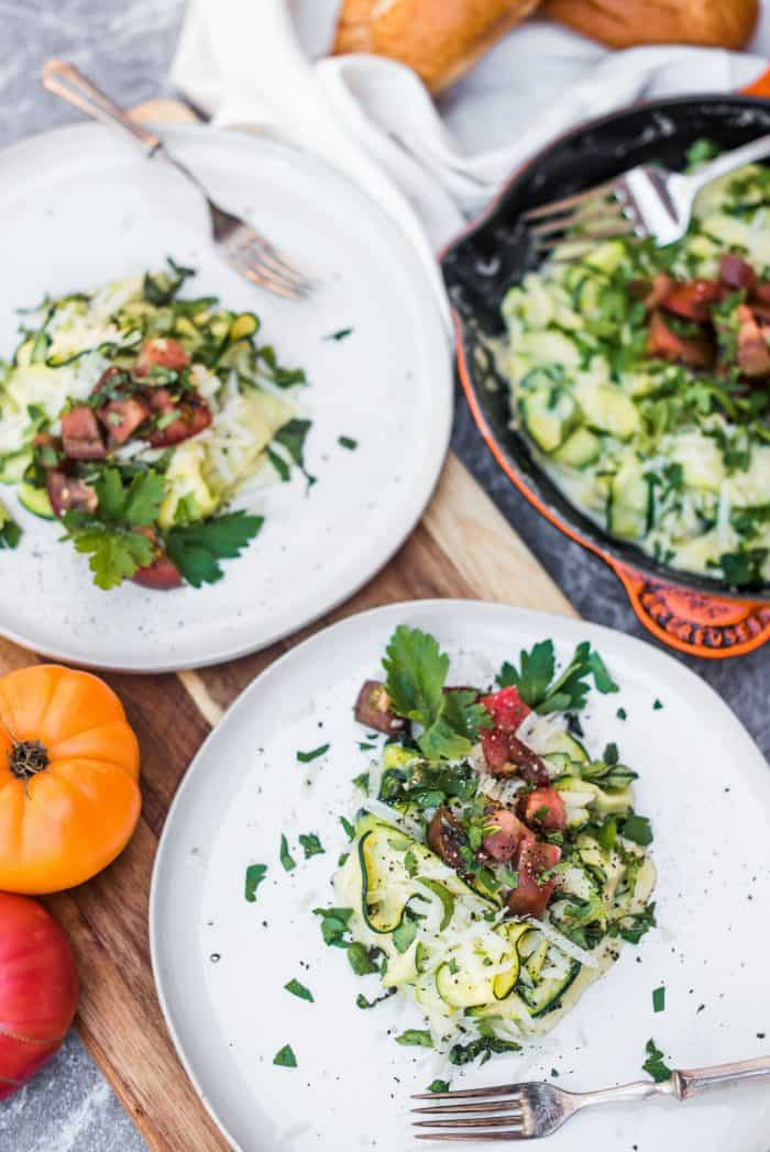 2 plates of cooked zucchini noodles with white sauce and tomatoes