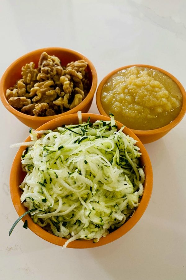 bowls of walnuts, applesauce, and shredded zucchini