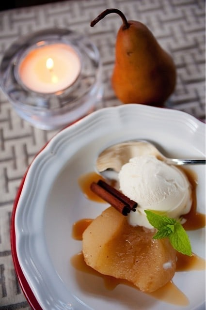 poached pear with ice cream garnished with cinnamon stick