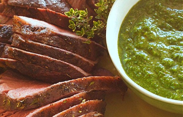 Chimichurri sauce in a white bowl with beef