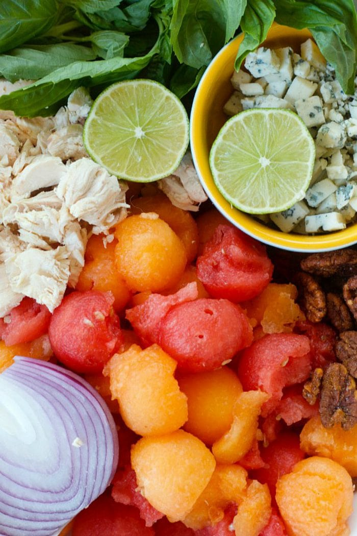 ingredients for chicken salad with melon balls, lime, and red onion
