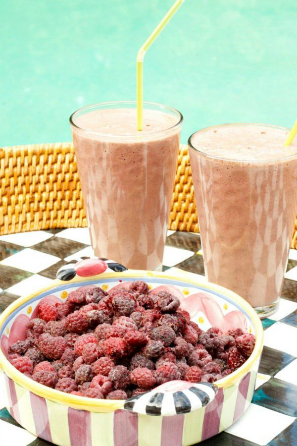 a bowl of raspberries and 2 smoothies