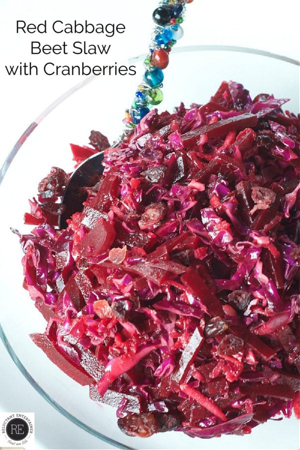clear bowl of Red Cabbage Beet Slaw with Cranberries and a spoon