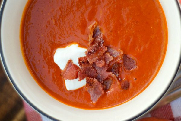 bowl of tomato soup with creme fraiche and bacon on top