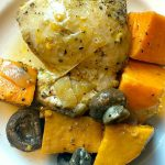 plate of cooked chicken thighs with mushrooms and sweet potatoes