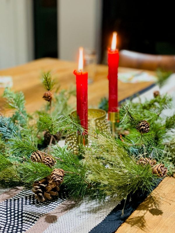 burning 2 red candles with green wreath