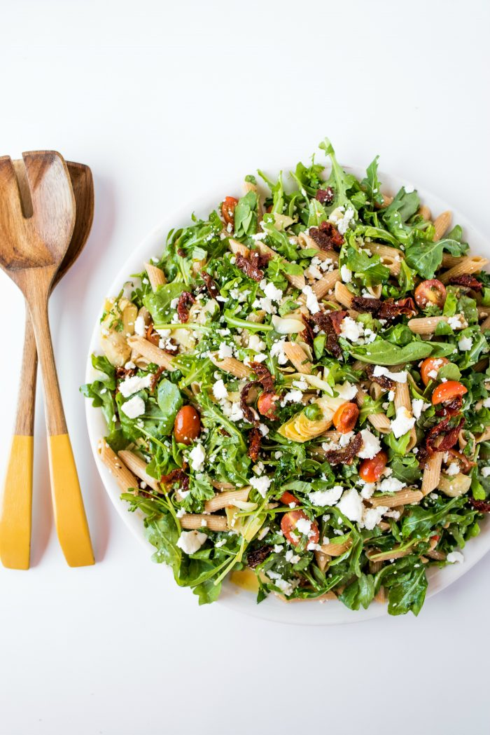 arugula pasta salad with serving spoons