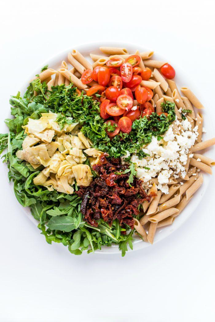 round plate of arugula pasta salad