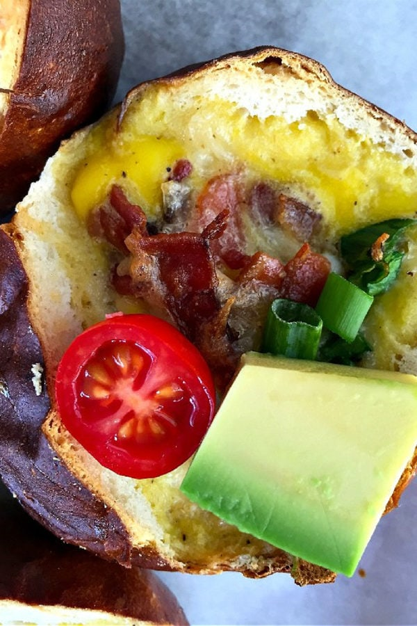 baked bacon and egg pretzel roll with avocado