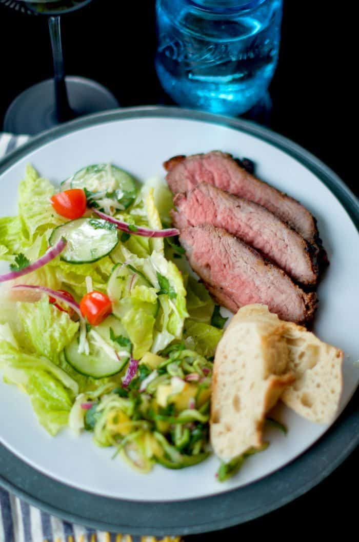 a white dinner plate with Grilled Garlic Pepper Tri Tip, salad, and bread