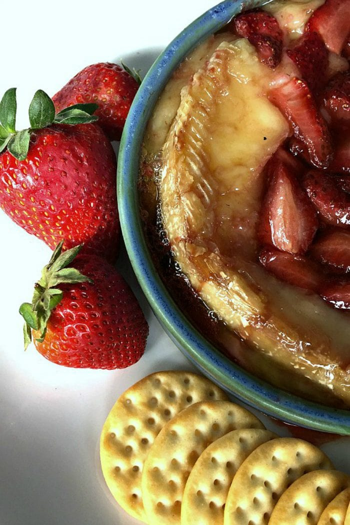 a closeup shot of hot brie with roasted strawberries