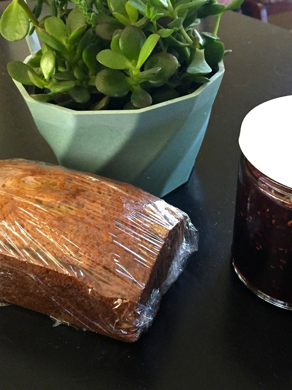 Sour Cream Banana Bread wrapped in plastic wrap with a jar of jam