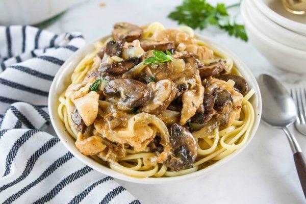a bowl of chicken marsala on pasta