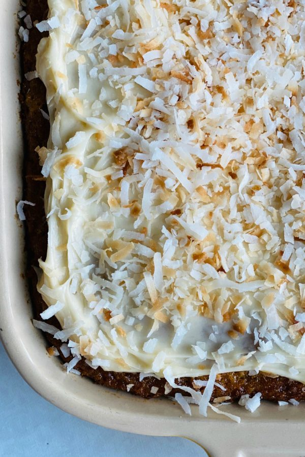 close up cream cheese frosting with coconut on a pineapple cake