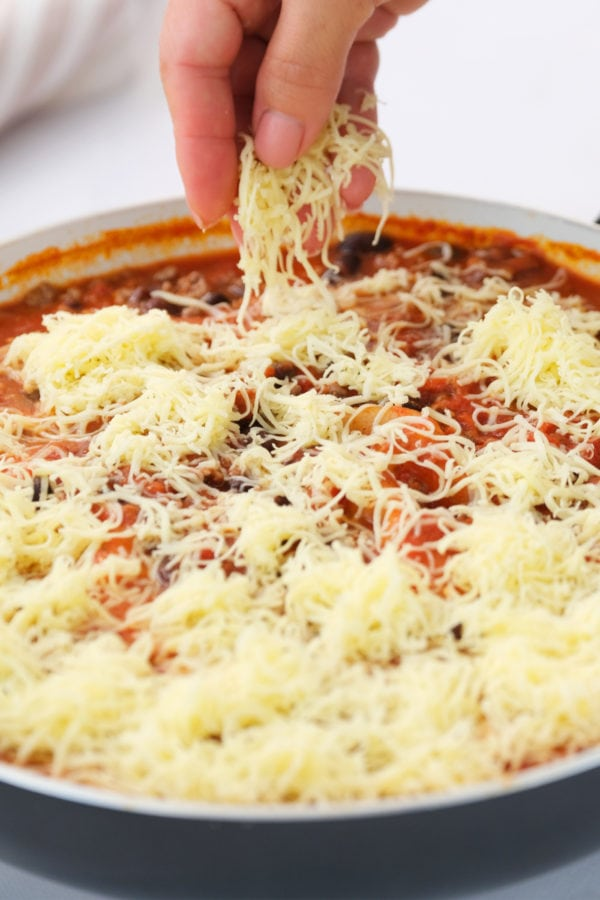 adding shredded cheese to Skillet Mexican Lasagna