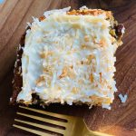 piece of pineapple cake with cream cheese frosting and toasted coconut
