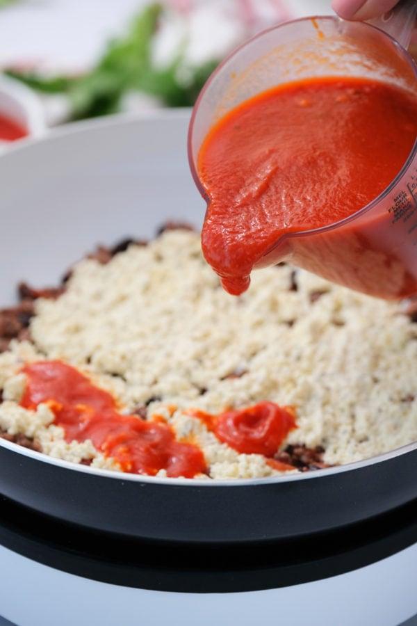 pouring marina on Skillet Mexican Lasagna