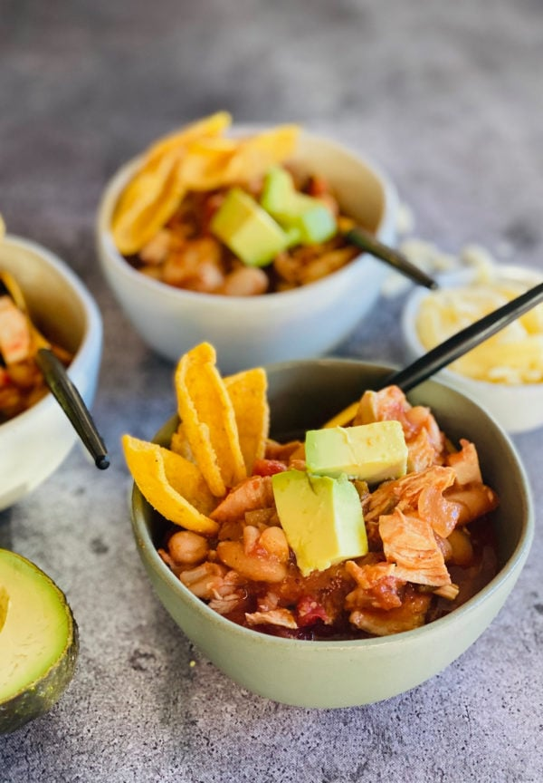 bowl of white bean chicken chili with Fritos and avocado