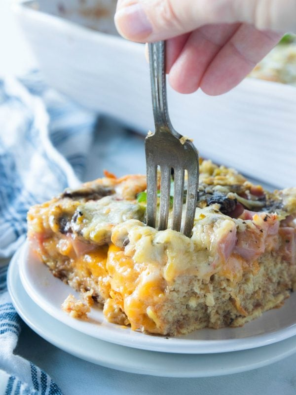 a fork in a square piece of baked ham breakfast bake