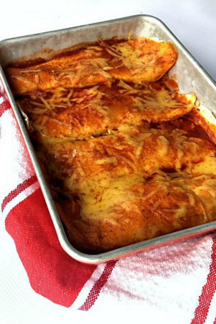 a pan of cheesy enchiladas with red sauce