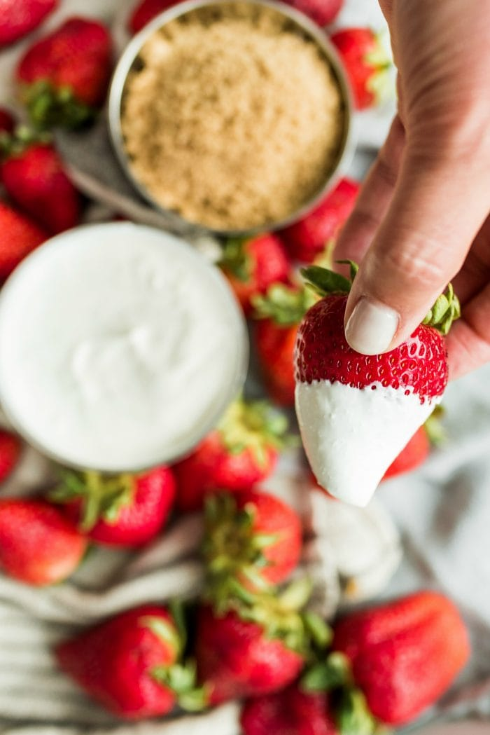 dipping a strawberry in a bowl of sour cream