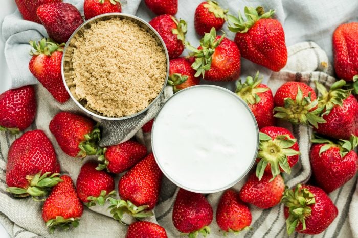 bowl of dark brown sugar and a bowl of sour cream, surrounded by fresh strawberries