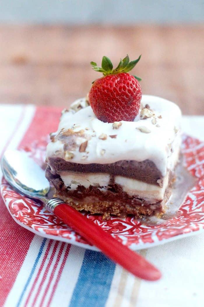 FrozenBanana Split Dessert on a pretty red platem garnished with a strawberry