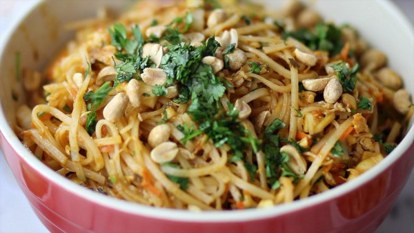 Red bowl of Pad Thai Salad garnished with peanuts and fresh cilantro