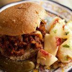 sloppy joe sandwich on a plate with fresh peaches
