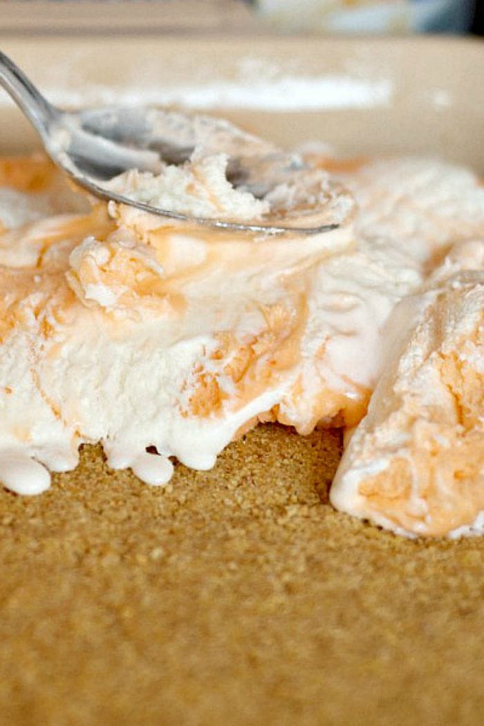 pressing down creamsicle orange ice cream on a graham cracker crust