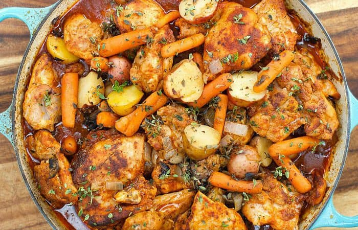 a dutch oven with paprika chicken thighs, carrots and potatoes