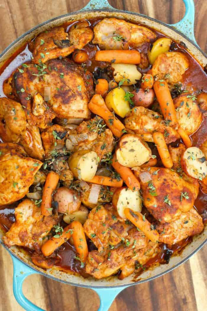 beautiful photo of paprika chicken thighs with potatoes and carrtots, cooked in a dutch oven