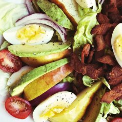 pear salad with sliced avocado, egg, and chopped bacon