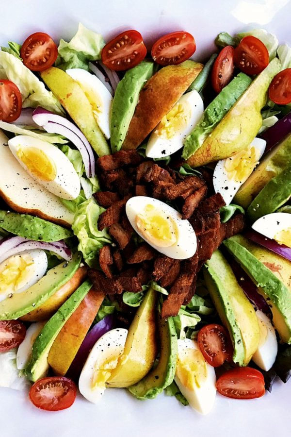 platter of sliced eggs, avocado, pear salad with crumbled bacon in the center