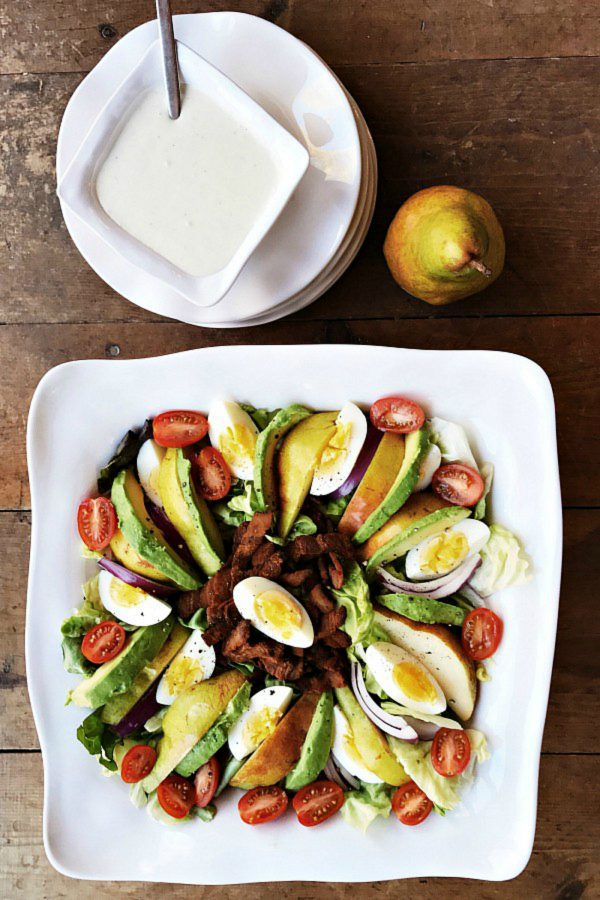 white bowl of pear and bacon salad with blue cheese dressing on the side